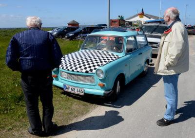 gammel blå bil med sort-hvide firkanter på motorhjelm